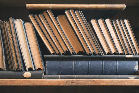 Old books in a vintage library shelves