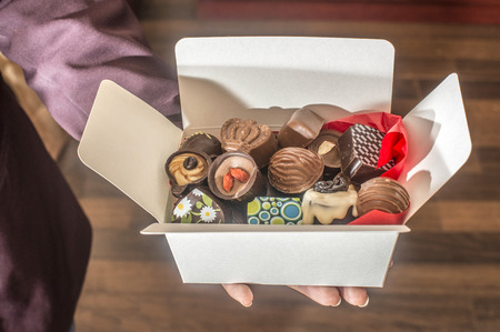 Hands holding a box of chocolates. Close up