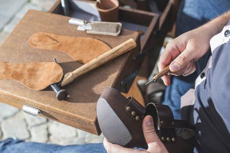 tienda de zapatos: Manos que hacen zapatos. Zapatero Foto de archivo