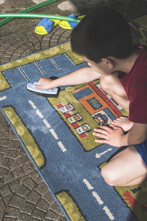 carpet clean: Child clean carpet. Exterior shot