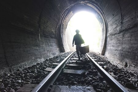street life: Child walking in railway tunnel. Vintage clothes