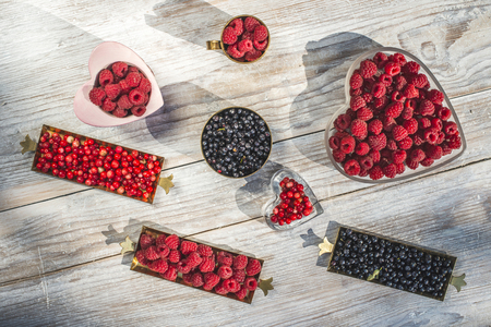 sweet background: Red and black raspberry and blueberry in bowl on wood