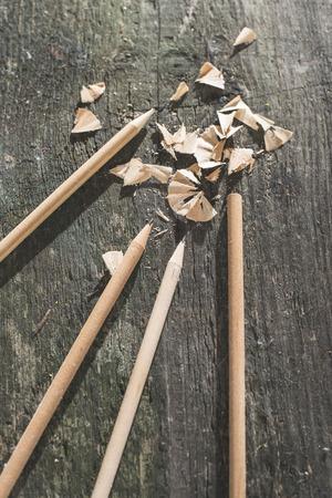 old desk: Vintage natural wooden pencils on dark wooden board