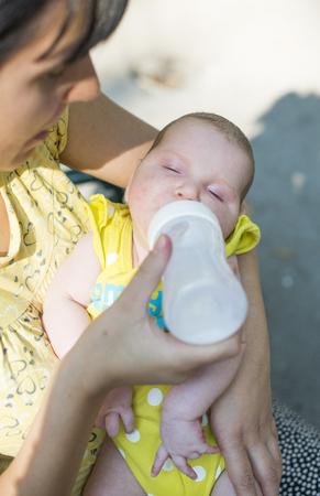 sucks: Baby sucks on a bottle. Baby in mothers hands