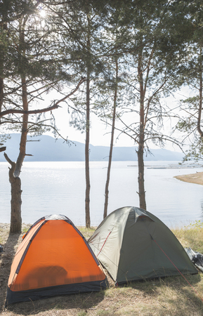 camping tent: Tents in the forest in front of mountain lake