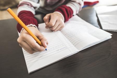 lapiz y papel: ni�o escriba en un cuaderno. Cierre de la mano y la pluma Foto de archivo