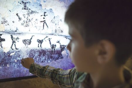 the mural: Child looks at aancient mural. Face