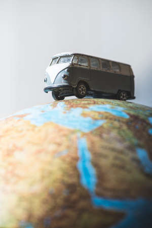 forced perspective: Vintage bus on globe. Miniature concept Stock Photo