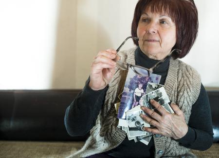 caucasian ancestry: Senior woman watching old photos. Sadness Stock Photo