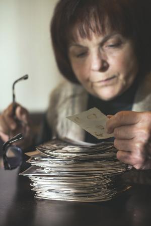 Senior woman watching old photos. Sadness Stock Photo
