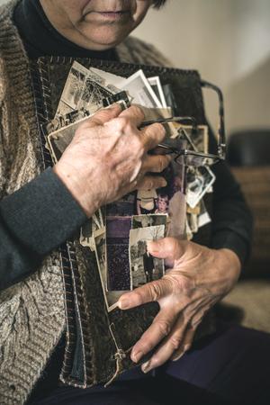 Ältere Frau, alte Fotos zu beobachten. Traurigkeit