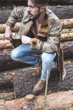 Les jeunes hommes sur les grumes dans la forêt. Cuir et un jean
