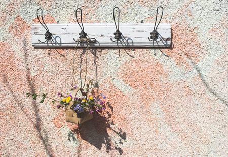 floral decoration: Flowers in the basket on hanger on a wall. Sunlight Stock Photo