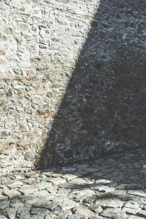 empedrado: muro de piedra de ladrillo viejo y carretera asfaltada