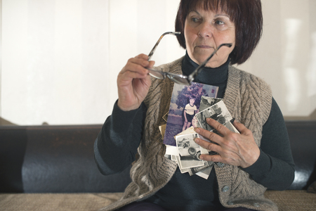 reminisce: Senior woman watching old photos. Sadness Stock Photo