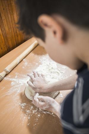 haciendo pan: Hacer pan en una cocina. Ni�o a hacer pan. Bolas de masa