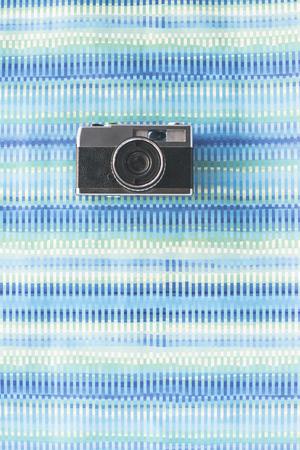 photocamera: Vintage photocamera on blue paper background.