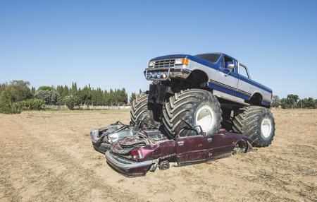 Monster truck over cars. Blue sky 스톡 콘텐츠