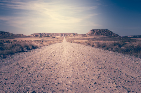 dirt: Woman walking on dirt road. Looking like a movie