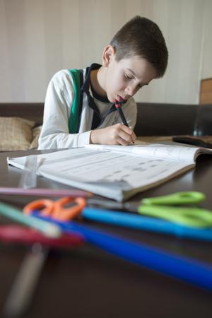 Bambino fare i compiti. Notebook per matematica. penna della stretta della mano. apprendimento Boy
