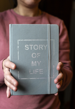 Woman hold notebook. Book notes for the Story of my life. Personal memoirs notes concept. Hands hold book.