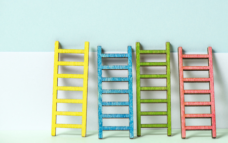 Multicoloured ladders on wall. Pastel tones. Concept for success and growth. Business metaphors. Фото со стока