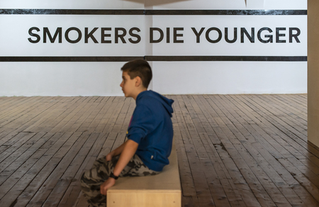 Teenager smoking and message on wall - Smokers die younger. No smoking concept with child. Casual clothes.