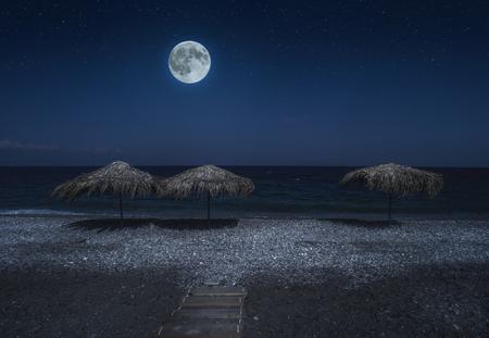Straw umbrellas on the beach in the night. Moonlight on sea. Night starry sky.