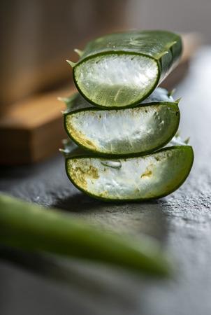 Aloe vera slices on dark background. Health and beauty concept. Closeup aloe pieces on backlight.