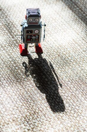 Vintage metal blue robot toy on sunlight. Futuristic concept with small mechanical robot toy walking on cloth surface.
