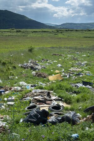 Heaps of garbage in the nature. Green grass and mountains on background.