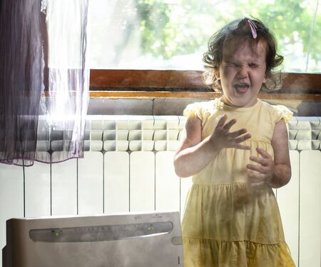 Little girl in a dusty room. Air purifier and coughing kid. Dust in the air. Allergy concept. 免版税图像 - 128382775