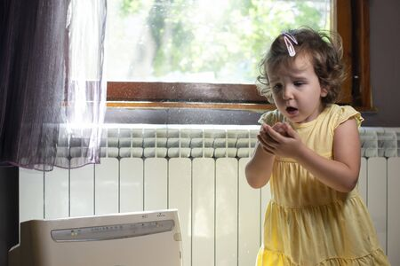 Little girl in a dusty room. Air purifier and coughing kid. Dust in the air. Allergy concept.