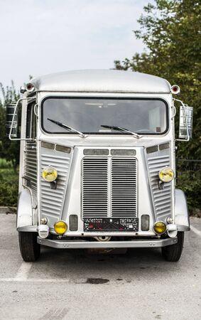 Old camper parked on asphalt road. Vintage travel concept.