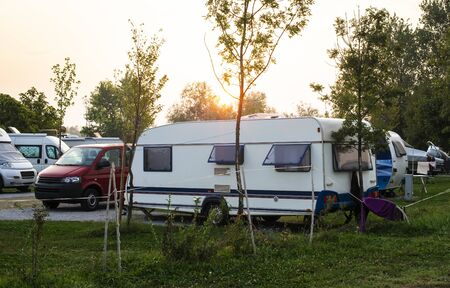 Caravans and campers on green meadow in campsite. Sunrise, rays on campers in the morning. Green grass. Outdoor concept for traveling and res in the nature. Stock Photo