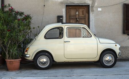 Small vintage italian car. Beige color old car in front of old house facade and flowers..