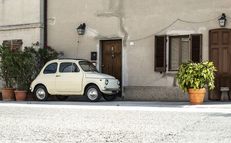 Small vintage italian car. Beige color old car in front of old house facade and flowers.. Reklamní fotografie