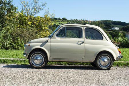 Vintage beige color car. Small old car. Italian car. Sunny day