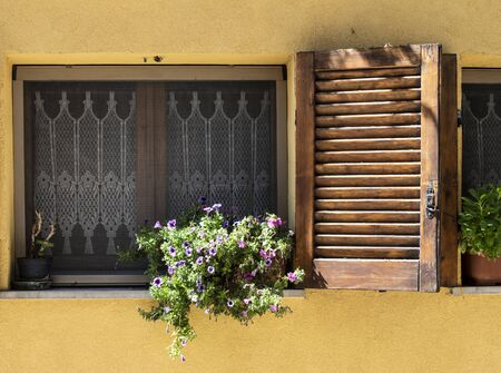 Typical italian facade with window. Italian house. Traditional style and ornaments. Flowers on the window.