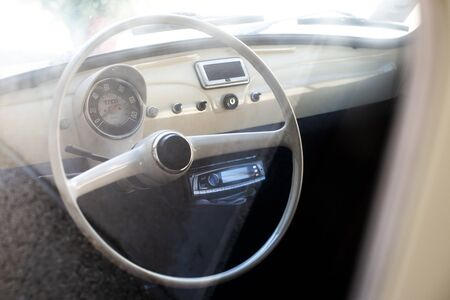 White interior of vintage car. White steering wheel.