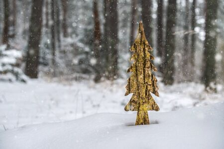 Wooden shaped pine tree in the snow in forest. Fir tree shape and shiny paint. Snowing in the forest. Gold colors Stock Photo