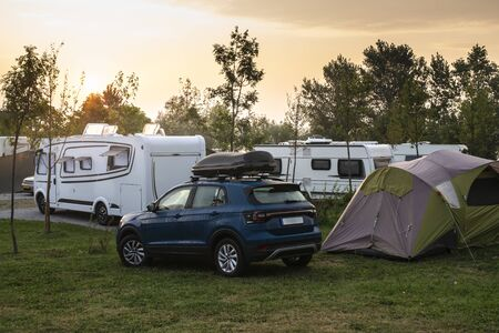 Caravans and campers on green meadow in campsite. Sunrise, rays on campers in the morning. Green grass. Outdoor concept for traveling and res in the nature. Reklamní fotografie