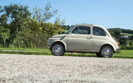 Vintage beige color car. Small old car. Italian car. Sunny day Reklamní fotografie