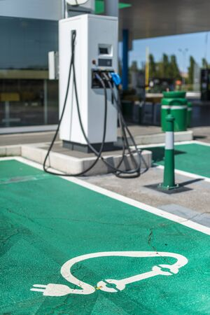 Electric charge station. Electric plug for charging cars. Car charging symbol painted on asphalt. Ecology fuell concept.