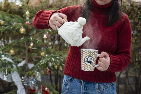 Woman pours tea with a teapot into a teacup. Christmas tree in the foreground. Teacup with Christmas ornaments. Steam comes out of cup of tea. Winter and Christmas concept. Exterior shot. 写真素材