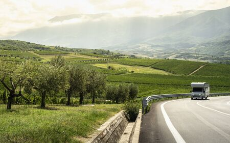 Asphalt road, vineyards and olive trees in countryside. Travel with camper. Wine and food travel concept. Italian agriculture.