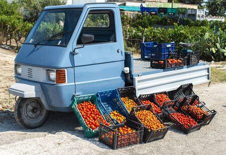 Pequeño camión apo italiano con tomates. Mercado callejero. Tomates de la venta del agricultor en la calle en Italia. Foto de archivo