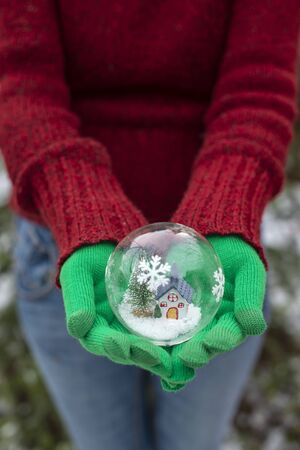 Crystal christmas ball with house and snow inside. Hands with green gloves hold transparent ball.