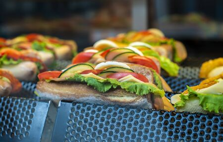 Sandwich on shelf in bar. Showcase light. Fast food with bread meat and vegetables.