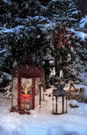 Christmas lamp with glass and candle inside in the night to pine tree. Snowing around the lamp. Snowflakes flying in the night.